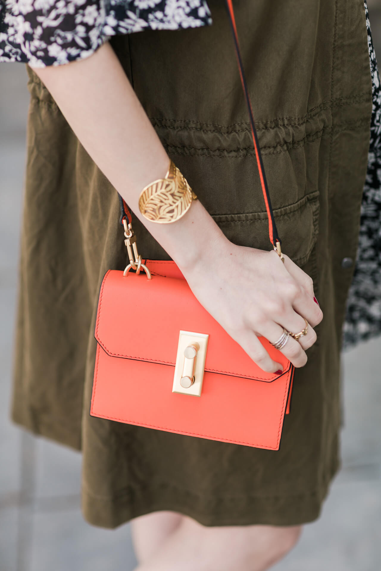 tangerine bag with utility vest and floral dress