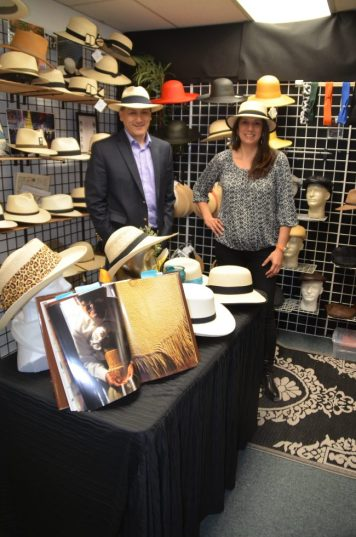 Yuri Parreno (left) and Ivonne Jurado (right) stand in Ultrafino's Lynnwood showroom. In the foreground, a book displays a master weaver creating the material for their hats.