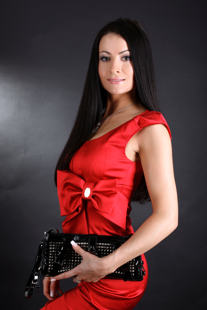 young woman in red dress with clutch bag