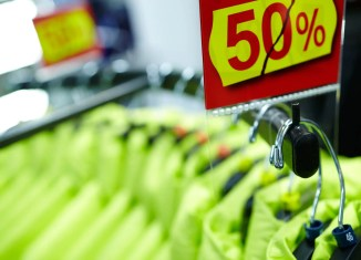 Clothes on hangers in the shop with fifty percent discount.