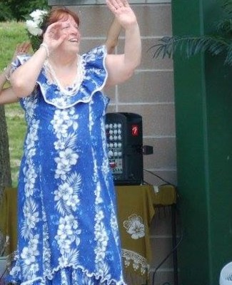 Photo: Pictured: Cindy, wearing a long, blue dress with white hawaiian flowers, spends her spare time hula dancing