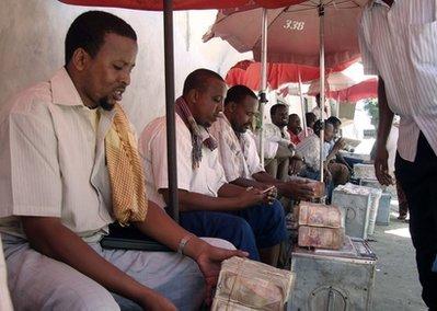Somali money changers sit with large amounts of money on display at the Bakara open market in Mogadishu, Somalia Wednesday, March 17, 2010.(AP Photo/Mohamed Sheikh Nor)