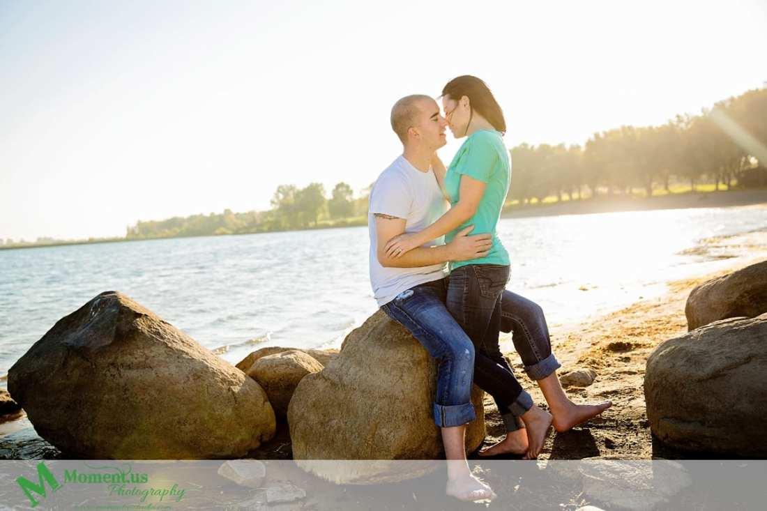 Cornwall engagement photographer - couple kissing on rocks by water