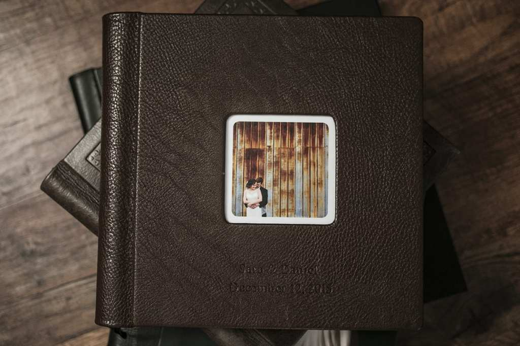 Embossed leather cover of Modern Ontario Wedding Album featuring couple cuddling in front of rusted metal wall