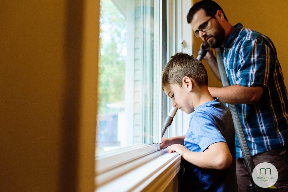 boy and dad vacuuming window