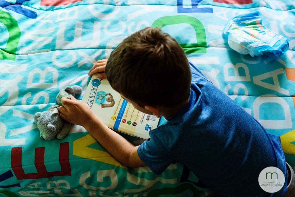 boy on bed with book and pull up