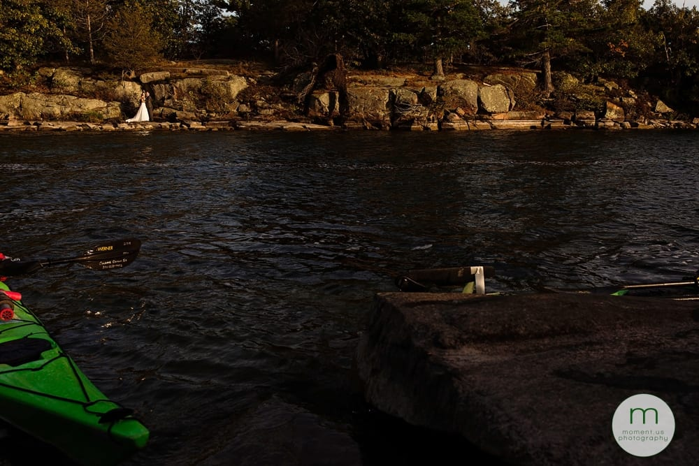 bride and groom on rocks with kayakers