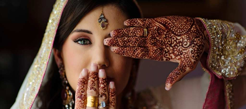 Cornwall bride with henna holding hand in front of face