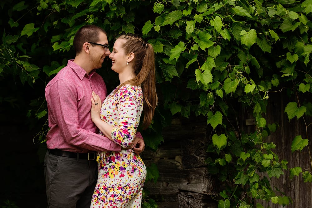Ontario wedding photographer - couple cuddling for Cornwall engagement photos next to family barn