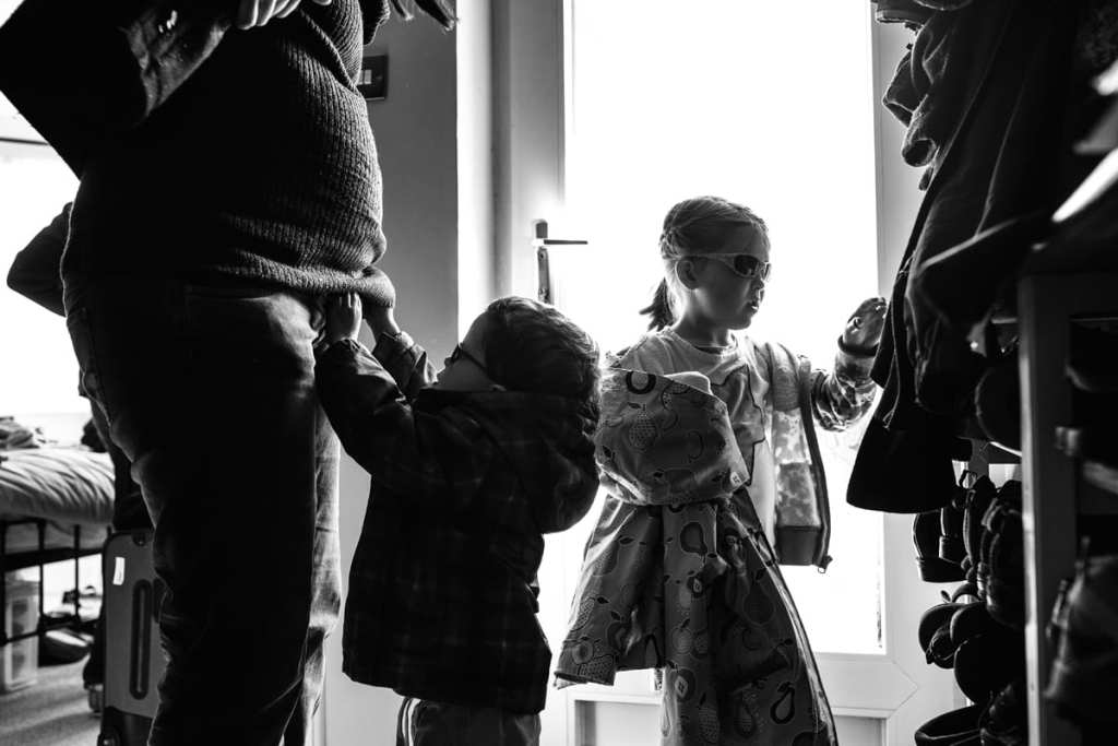 children and mother getting ready to leave house during London family photography session