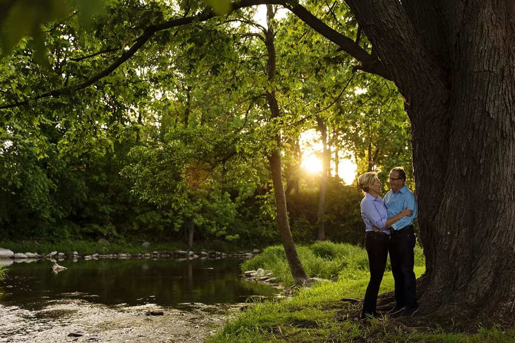 Couple standing under tree next to river