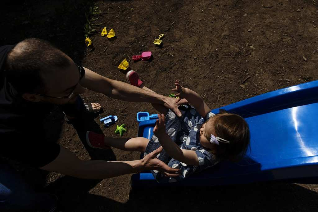 dad catching daughter on slide during family portrait session