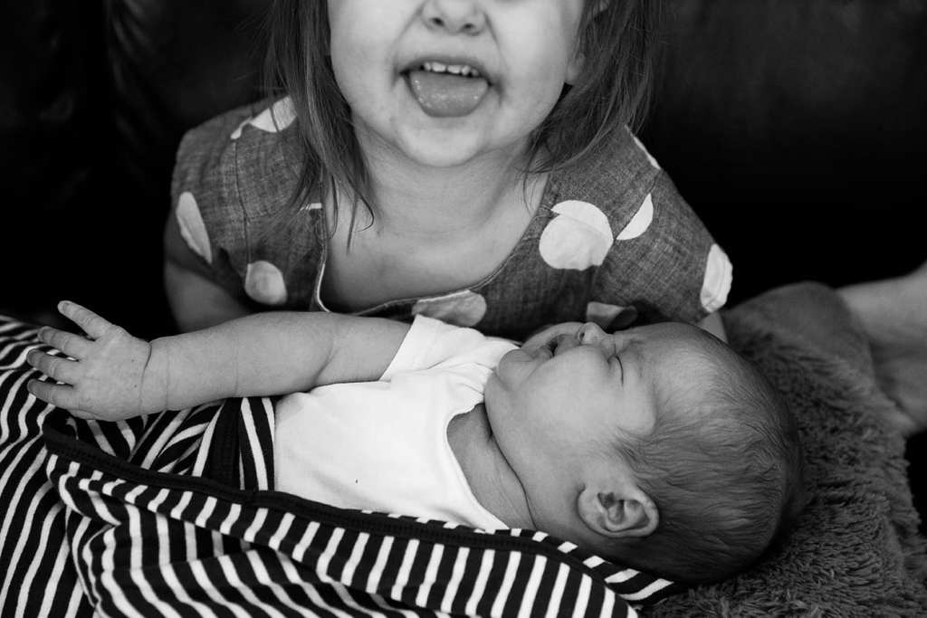 sister excited about holding brother during family portrait session