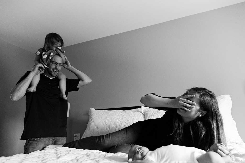 mom laughing at daughter on dad's head during candid Cornwall family portraits session