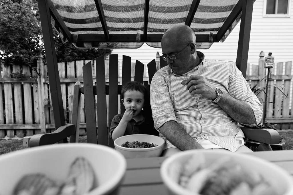 little boy and dad eating snacks on swing