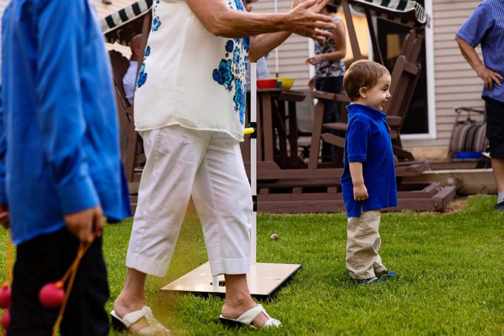 little boy in blue shirt outside with family during candid cornwall family photography session