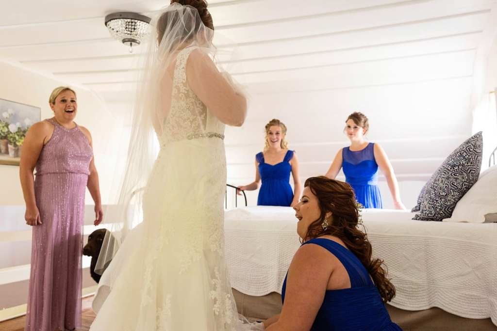 Bride with mother and attendants in royal blue getting ready in country bedroom