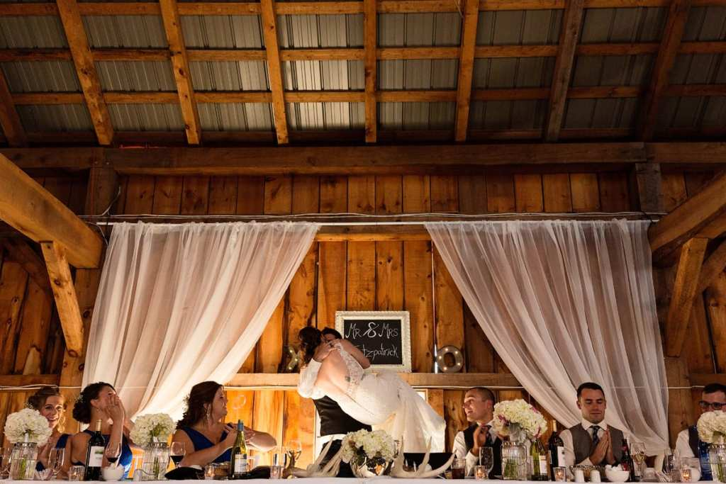 Groom picking up bride at head table with wedding party cheering