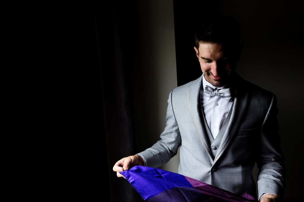 Groom in grey suit folding blue and purple pocket square