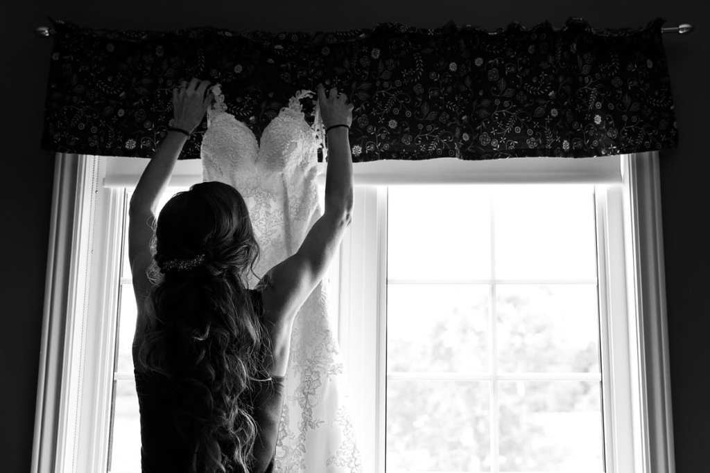 Bride hanging up wedding dress in front of window