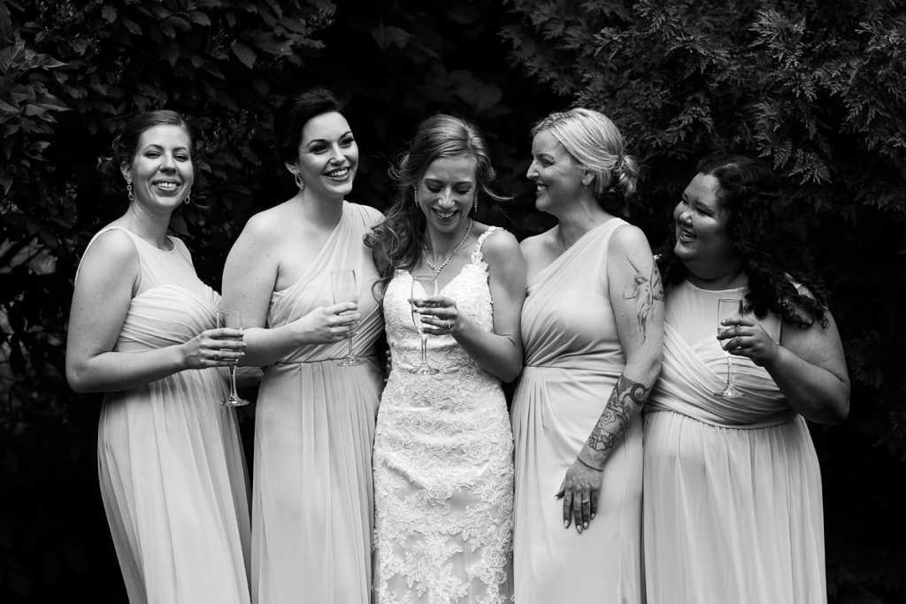 Bride with attendants sharing glass of champagne