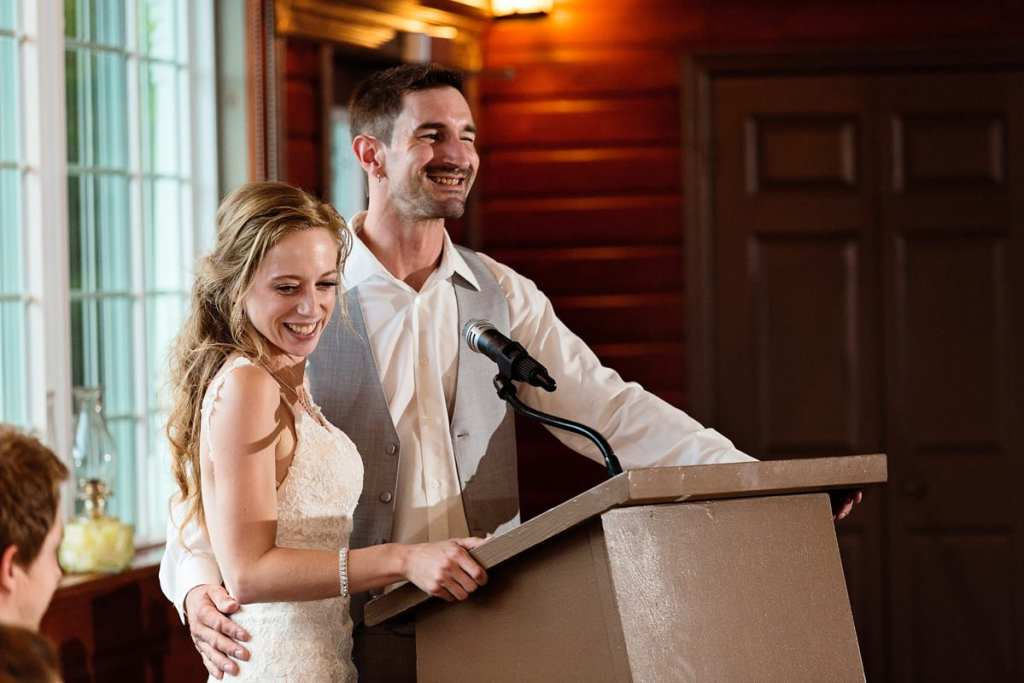 Newlyweds standing at podium for wedding speech
