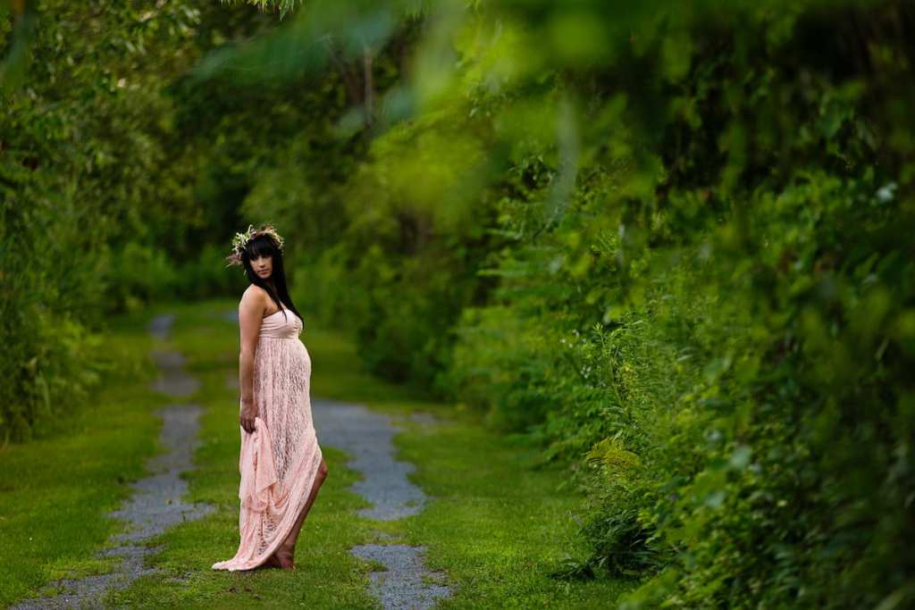 Bohemian woman in blush gown on lush green trail