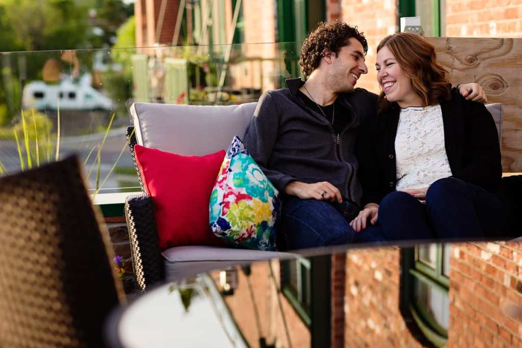 Happy couple on colorful patio couch of modern loft apartment