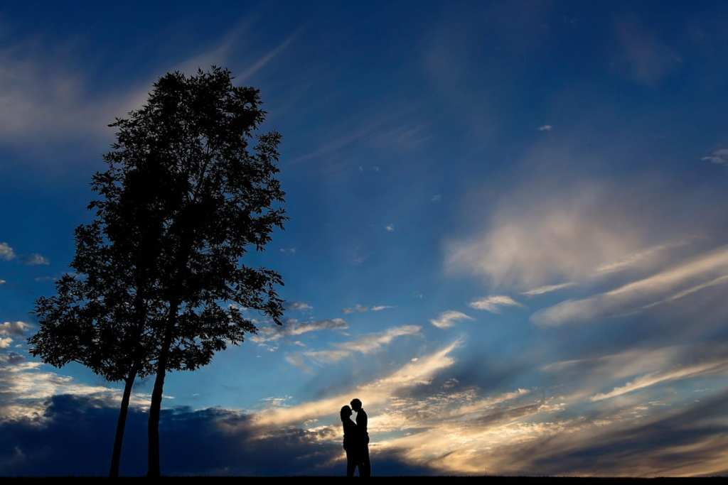 Kissing couple silhouette against blue sky and beautiful clouds