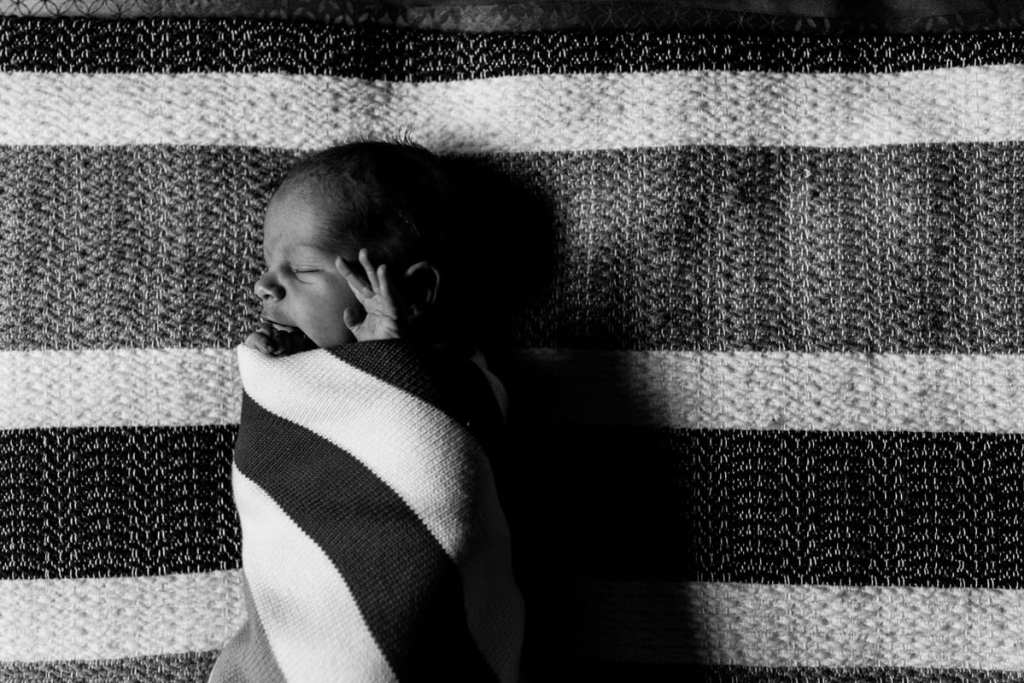Newborn baby boy in striped swaddle