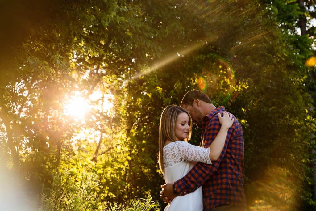 Woman with arm around man's shoulder in sunlit rural Cornwall engagement session