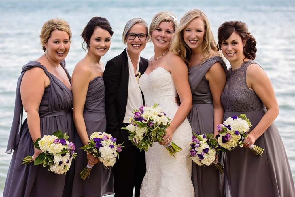 brides with bridesmaids in grey taupe dresses on waterfront dock
