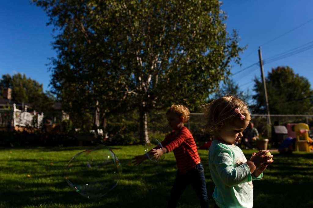 little boy and sister playing with bubbles in backyard