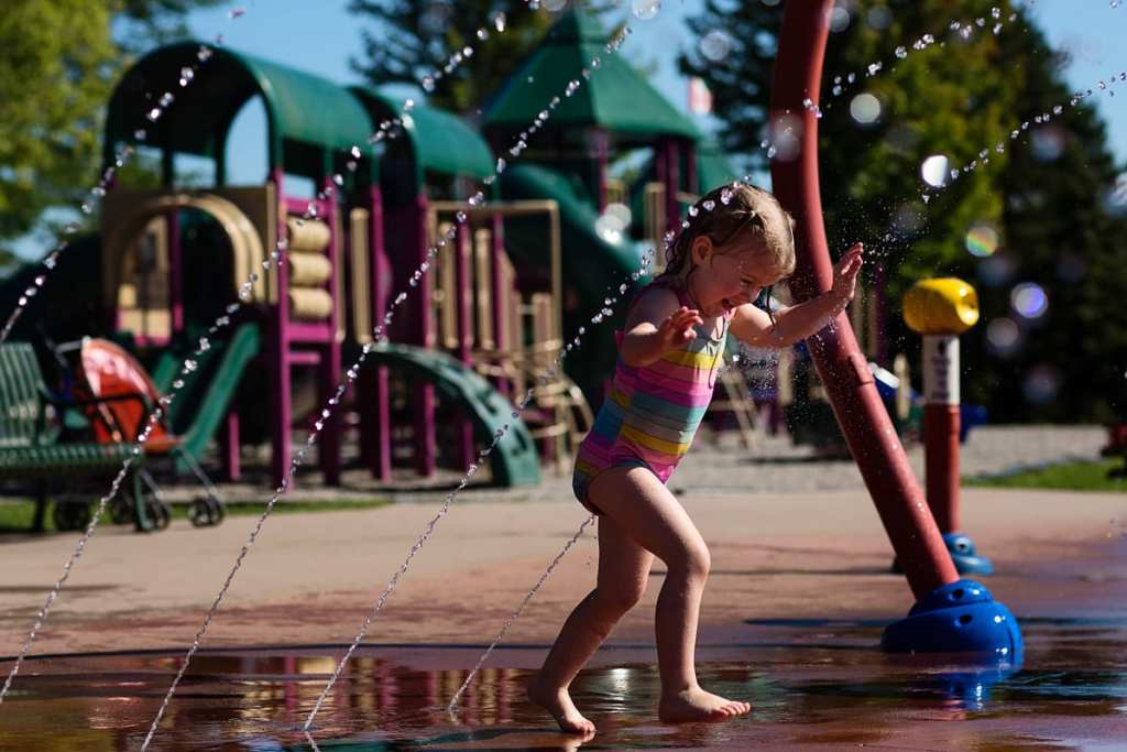 little girl in brightly coloured bathing suit playing in splash park