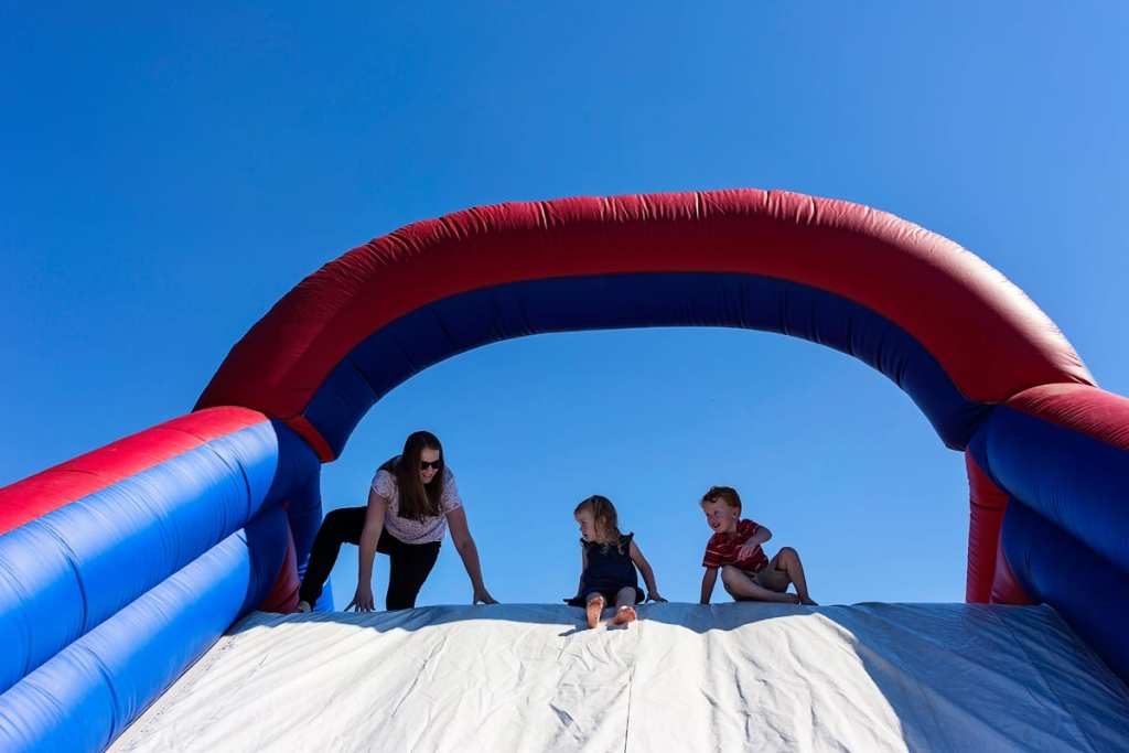 Mom sliding down inflatable slide with boy and girl