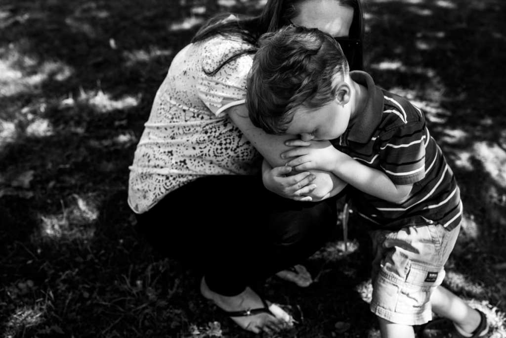 little boy in striped shirt and shorts being comforted by mom