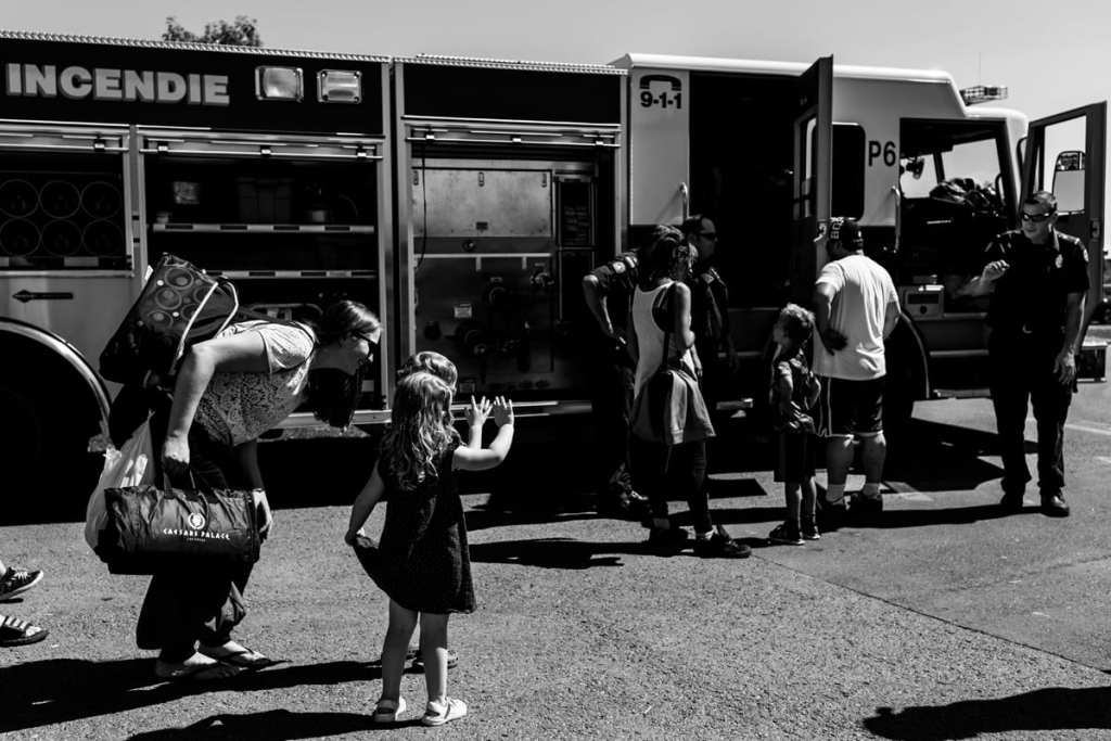 little boy and girl waving at firefighters beside fire truck