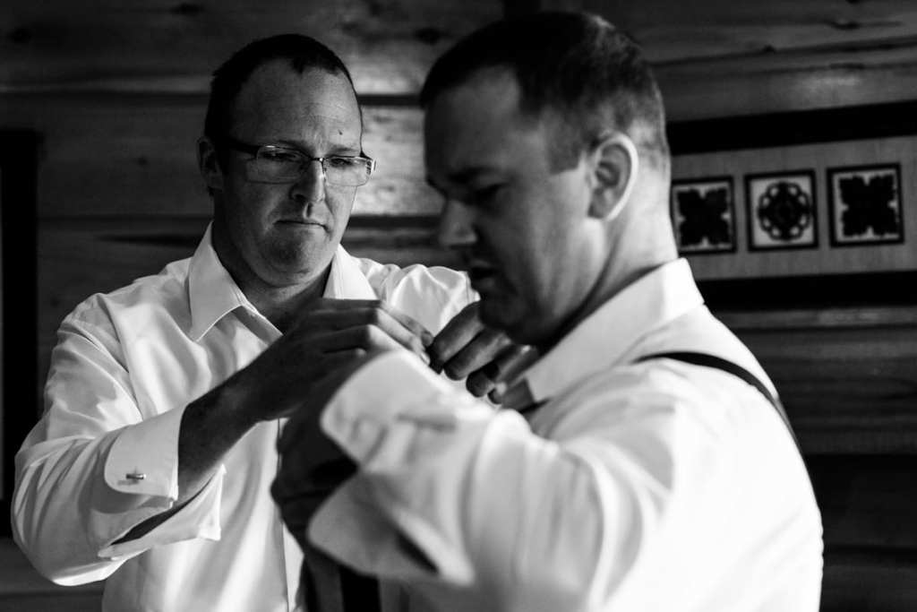best man and groom during wedding prep in rustic cabin at Calabogie