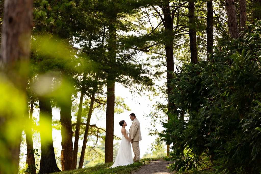 Bride and groom on path in sunlit trees at intimate Calabogie wedding