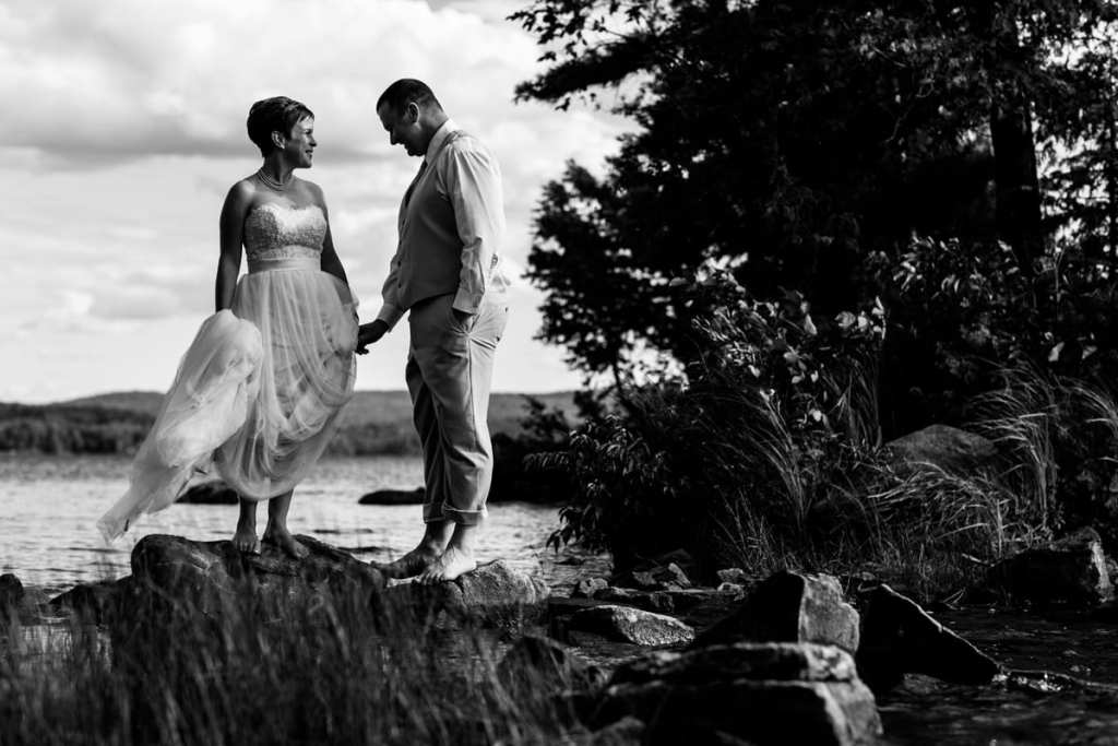 barefoot bride and groom holding hands perched on rocks in Calabogie wedding