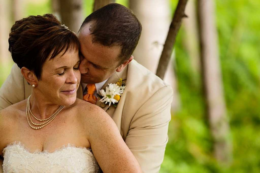 Groom kissing bride's cheek at summer Calabogie wedding
