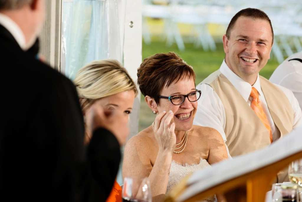 bride and groom laughing during speeches at intimate lakeside wedding