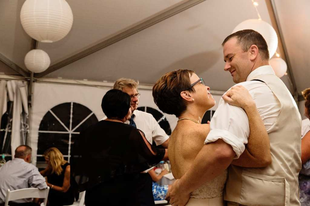 bride and groom dance amongst guests at tented lakeside wedding reception