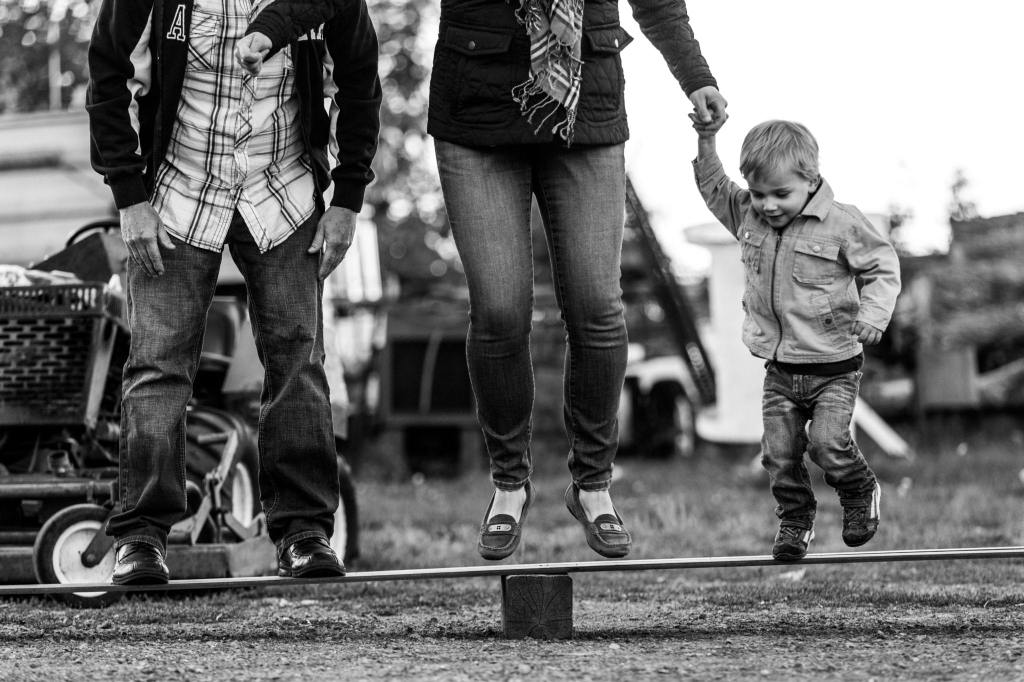 young boy and parents jumping on wooden board