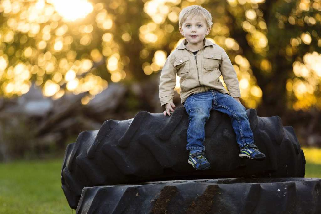 young boy in jeans and jacket sitting on tractor tire in golden hour fall family session