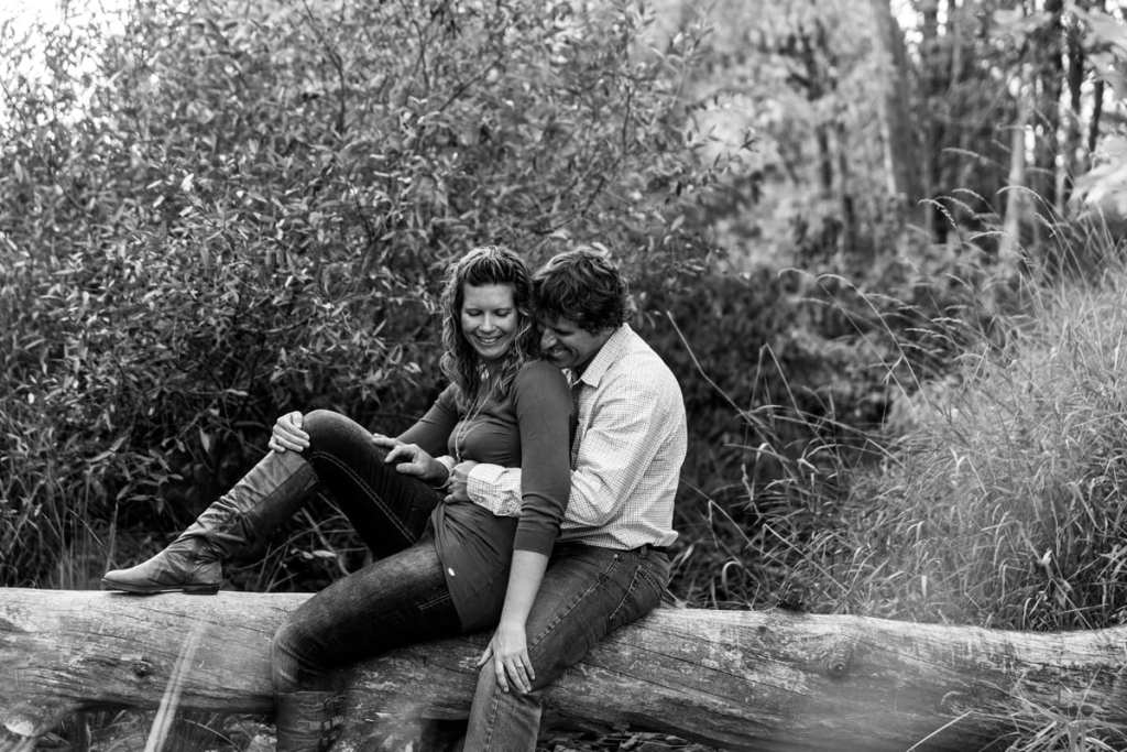 woman leaning on fiance on downed tree trunk in summer engagement session