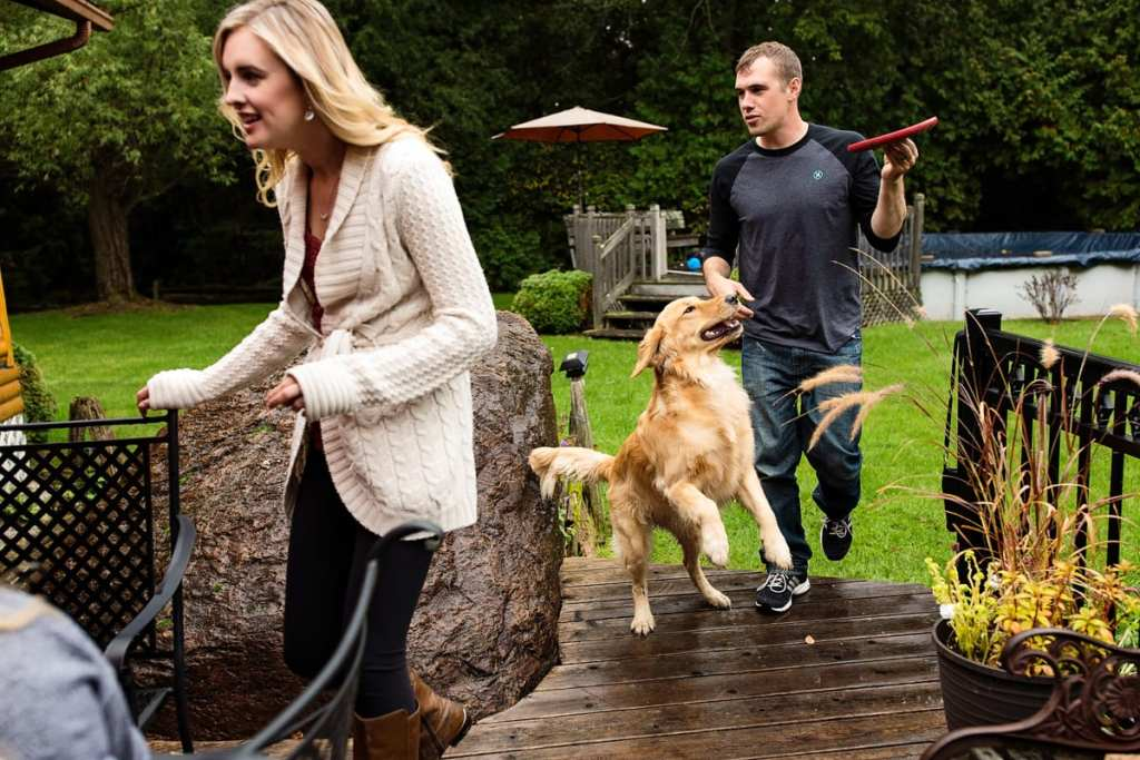 young couple playing with dog and joining family on patio in casual family session