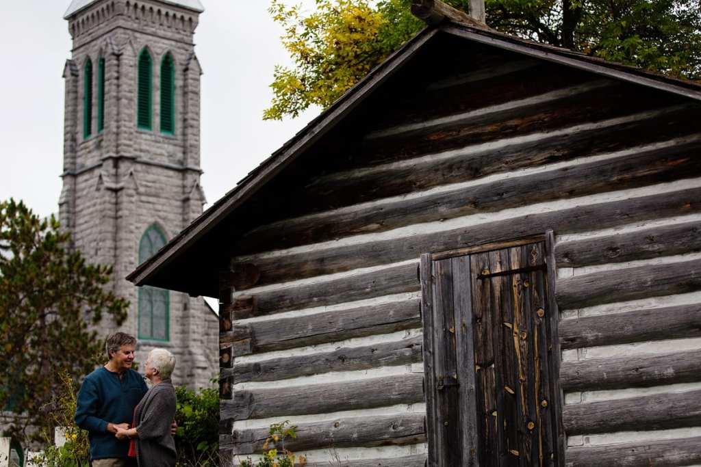Couple beside old log cabin with church in background during Ontario Casual Family Portraits