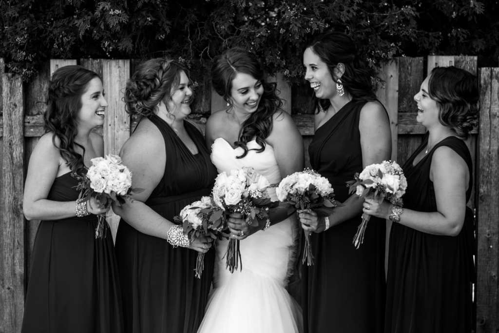 bride laughs with bridesmaids in front of fence