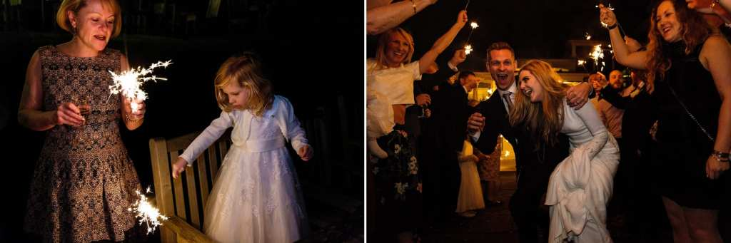 Little girl plays with sparkler while bride and groom make a sparkler tunnel exit during reception at Rhinefield House